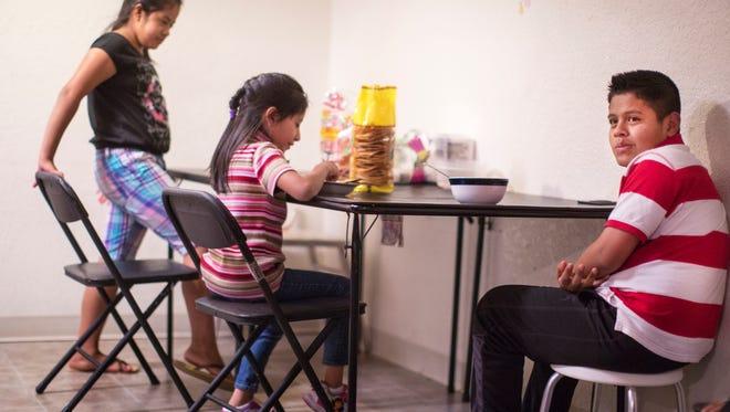 The children of Modesta Escalante prepare for dinner in their apartment in Hamilton, Ohio.