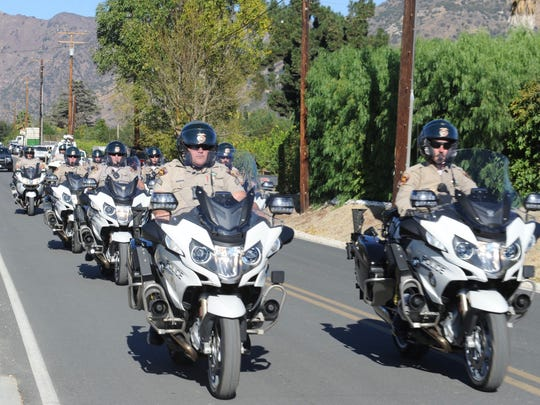 This file photo shows a motorcade arriving in Fillmore in December 2017 to escort the body of Cal Fire engineer Cory Iverson, who died while battling a flare-up of the Thomas Fire.