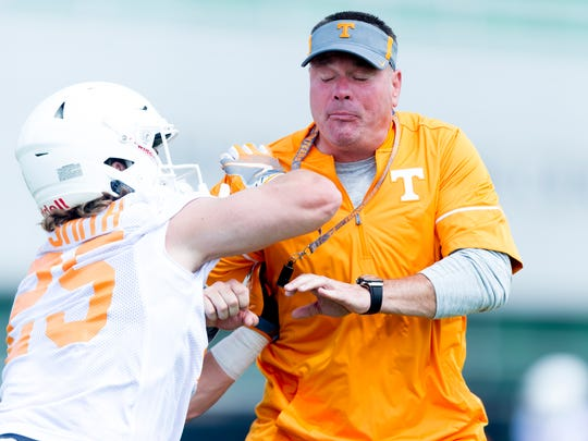 University of Tennessee Head Coach Butch Jones does a drill with University of Tennessee's wide receiver Josh Smith (25) during Tennessee Volunteers fall practice at Anderson Training Facility in Knoxville, Tennessee on Saturday, July 29, 2017.