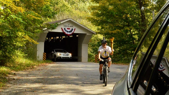 Bret Rinehart rides his bike through the 1874 Covered Bridge on Oct. 6, 2016, near Adams Mill in Carroll County.