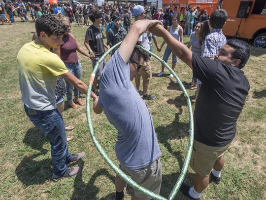 Brenden Ayres passes a hula hoop during a game as Exeter High School students were treated to a last-minute concert Wednesday, May 10, 2017. Students made t-shirts, painted vinyl albums and listened to several bands including the Plain White T's.