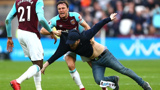 Mark Noble of West Ham United clashes with a pitch invader.