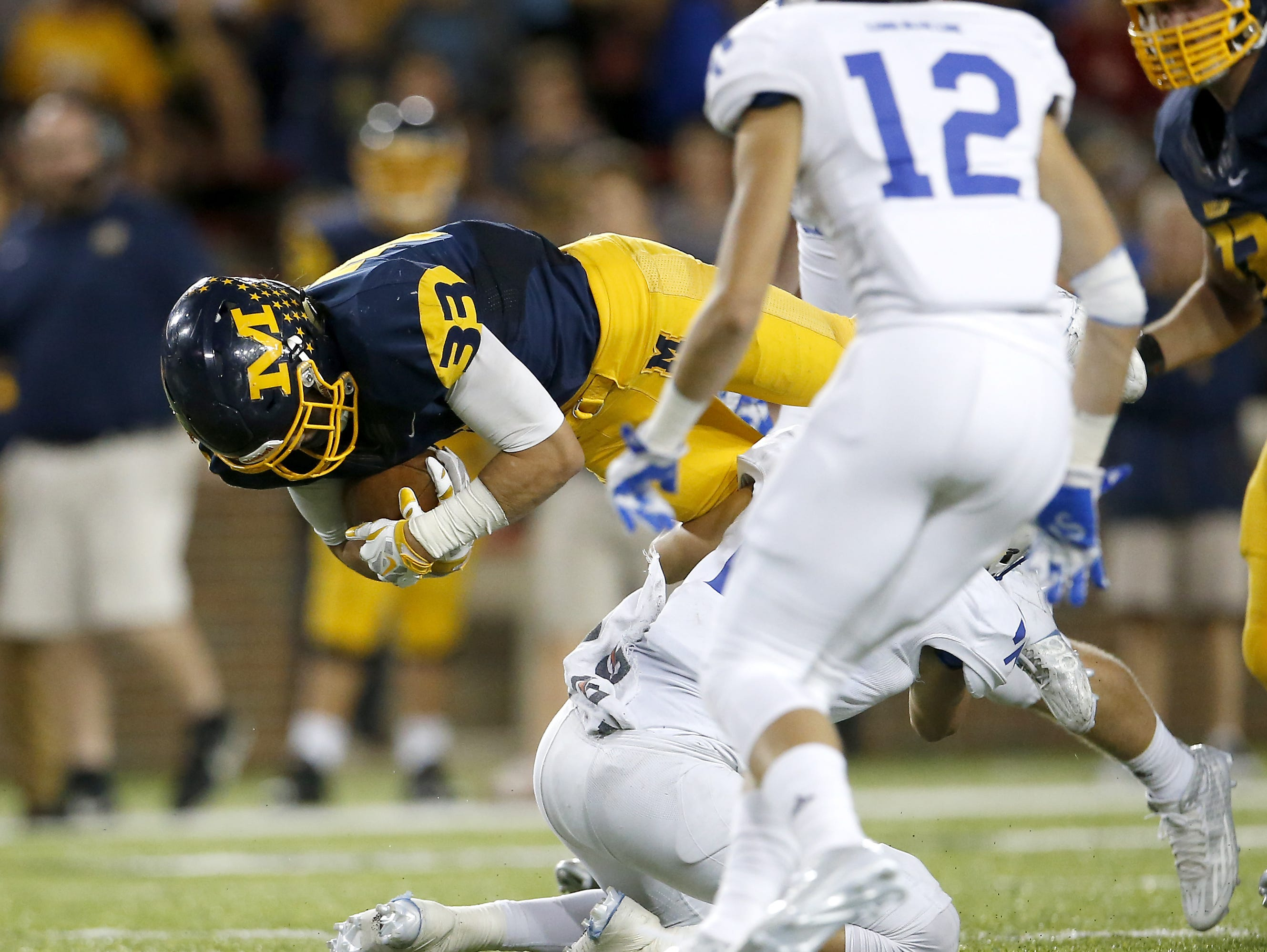Moeller running back Hunter Hughes leaps for extra yards on a run in the second quarter during the high school football game between the Moeller Crusaders and St. Xavier Bombers, Friday, Sept. 25, 2015, at Nippert Stadium in Cincinnati, Ohio.