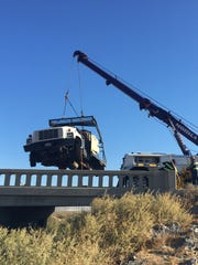 A tow truck lifts a utility truck that crashed on Highway