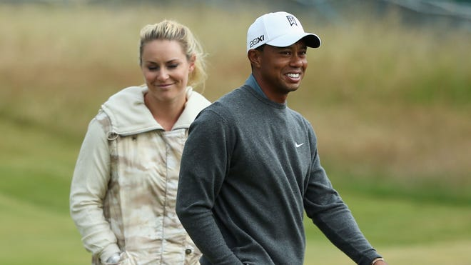 Lindsey Vonn walks with Tiger Woods during a practice round before the British Open in July.