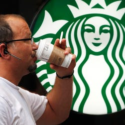 A man drinks a Starbucks coffee in New York.