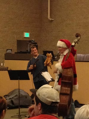 Graham Marshall, left, holds the Grinch's dog up for the audience to see as his father, Scot Marshall, tells the Grinch's tale Nov. 26 in the Fernley City Council chambers.