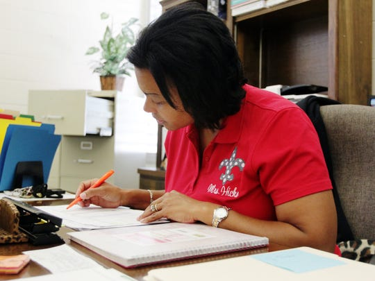 J.W. Faulk Elementary Principal Jamilah Hicks looks through teacher applications in her office in 2014. Hicks and her husband, Vincent Hicks, say they have learned more about being educators from each other.