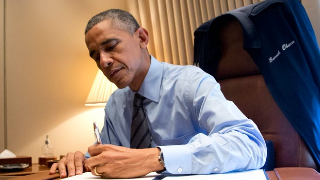 President Obama signs two presidential memoranda associated with his actions on immigration in his office on Air Force One as he arrives at McCarran International Airport in Las Vegas on Nov. 21.