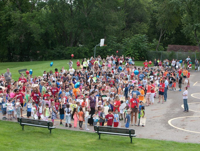 """Students of Perkins Elementary School gather on the playground to prepare for the annual """"Back to School"""" parade around the neighborhood on Friday morning, August 22, 2014."""