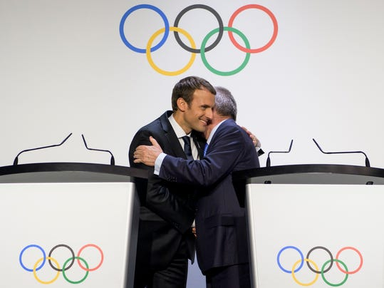 French President Emmanuel Macron, left, shakes hands with International Olympic Committee (IOC) President Thomas Bach during a visit of the Paris 2024 Candidate City delegation, at the Olympic Museum, in Lausanne, Switzerland, Monday, July 10, 2017. (Jean-Christophe Bott/Keystone via AP)
