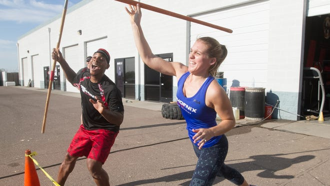 Jodie Perry, right, throws a spear while Phoenix Evolution OCR Training owner Lashay Marks tries to distract her during obstacle course training, Saturday, September 12, 2015, in Chandler Ariz.