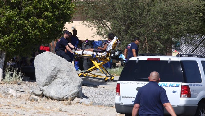 A woman is wheeled away on a gurney following a shooting in Desert Hot Springs.
