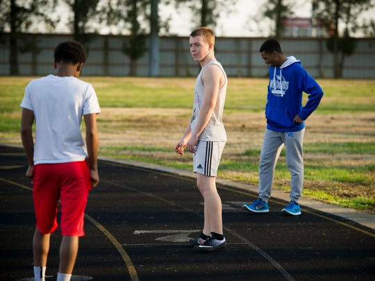 Adrian Kjellen, 17, of Nykšping, Sweden, center, lines up on the track with teammates, Isaiah Burkins, 15, of Henderson, left, and Jordan Smith, 16, right, also of Henderson, during track practice at Henderson County High School, Wednesday, March 8, 2017. Kjellen is an exchange student currently living with the Troutman family in Henderson.