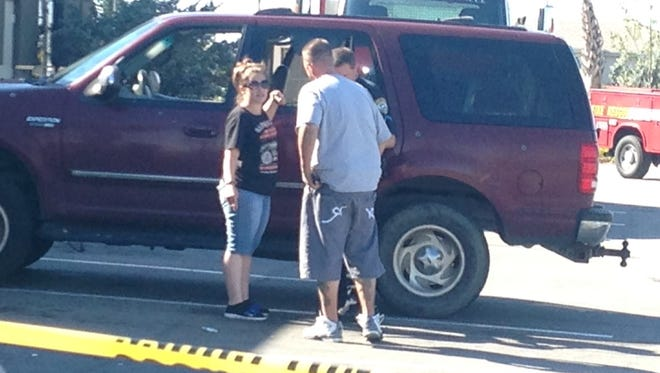 A Cape Coral police officer talks to people next to an SUV that was shot at in the parking lot of a Dollar General