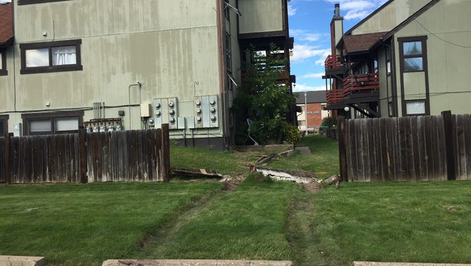 Police say a woman used a front-end loader to bust a fence down and then used the arm of the excavating vehicle to climb into an upper-level apartment.