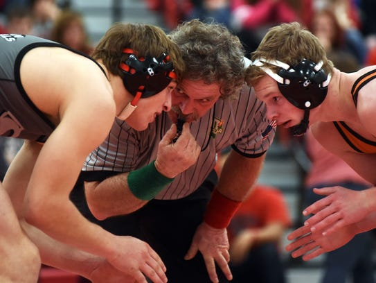 Official Okey Woodard talks to Sheridan's Cody Neece during his 182-pound match against New Lexington's Jacob Vance in suburban Thornville. Woodard is one of only three wrestling officials from Muskingum County.