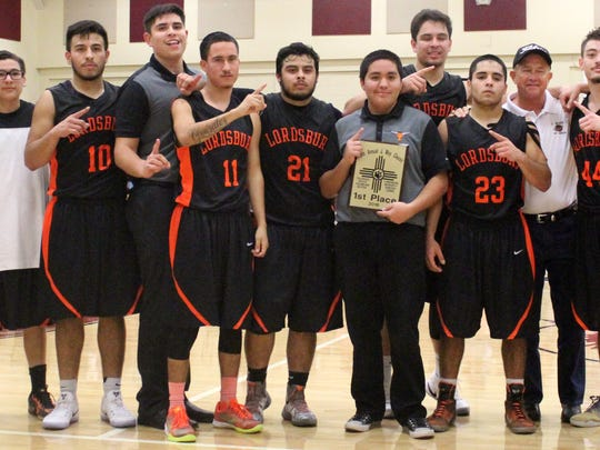 The Lordsburg Mavericks alongside Johnny May pose with their Johnny May Classic championship plaque Saturday night.