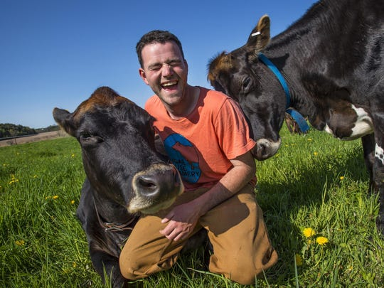 Henry Cammack of Henry's Dairy visits with two of his milkers, Jackie, left, and Patches at Bread and Butter Farm in Shelburne on Friday, May 20, 2016. Henry's Dairy is one of several small enterprises under one roof at the farm.