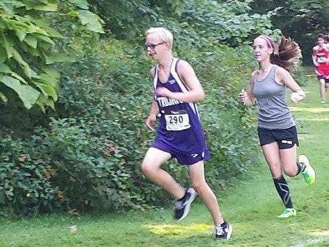 Olivia Reynolds, right, runs with Glen Este's Aaron Westerndorf after her race to guide the freshman around the course.