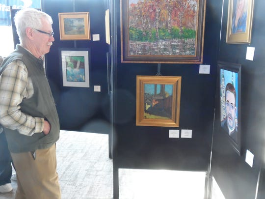 Tommy Faulk looks at artwork at the Contemporary Artists' Guild's Bank Show on Sunday. He is a member of the guild but did not have art on display in the show.