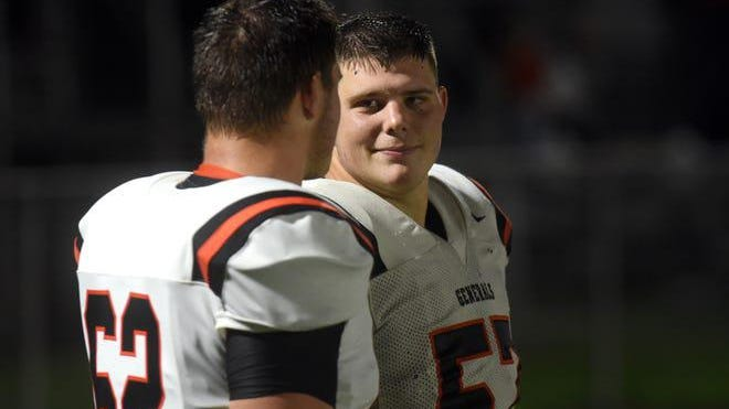 Bryce, left, talks to his brother Zach, during the closing minutes of Ridgewood's 42-7 win over Sandy Valley last Friday. The twin borthers are two-way starters on the offensive and defensive lines. Sam Blackburn/ Coshocton Tribune