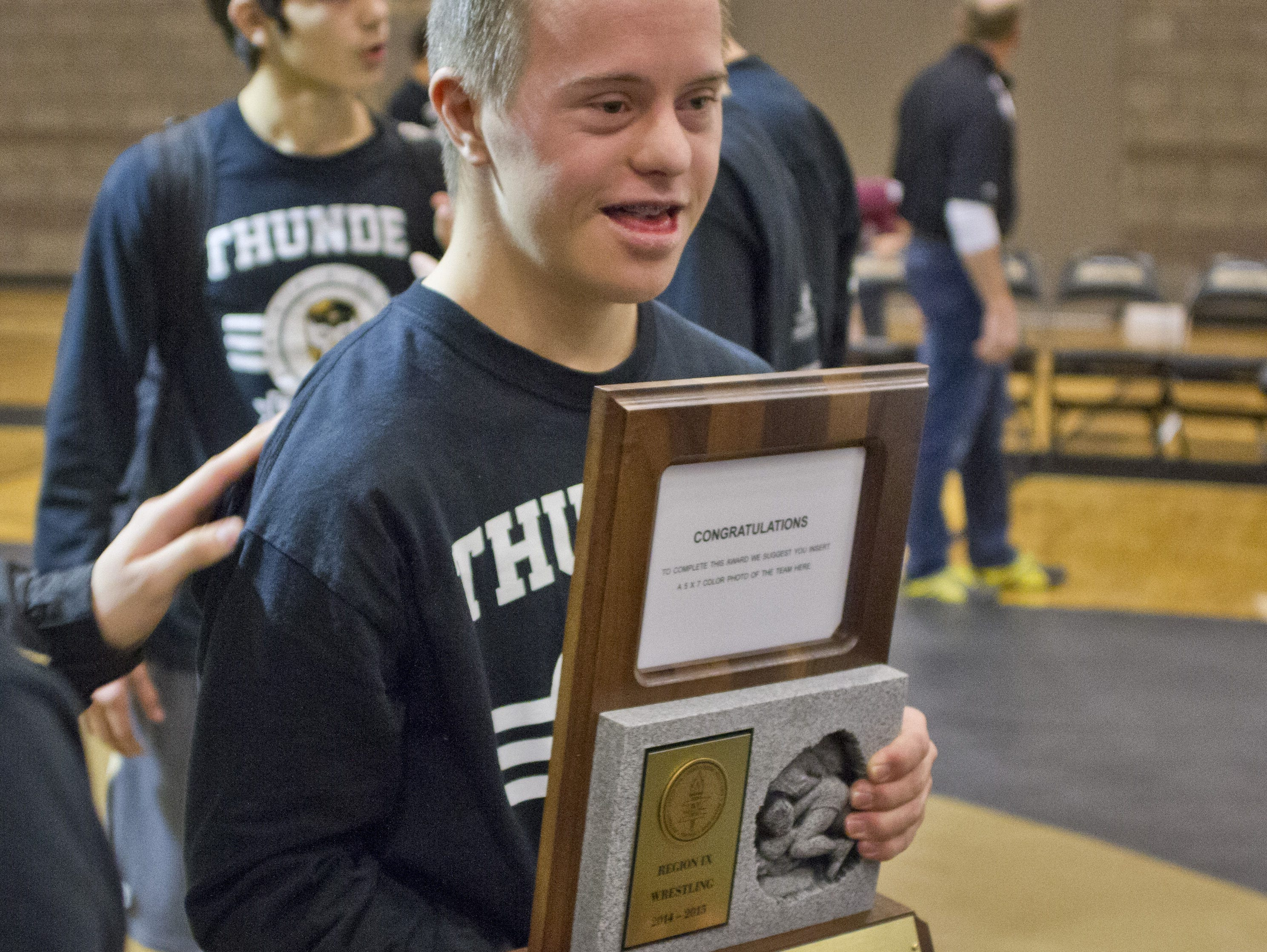 Dallin Birch from Desert Hills poses with the Region Championship trophy after starting the night by winning his match Thursday, Jan. 29, 2015.