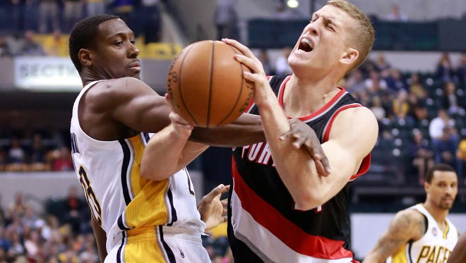 Indiana Pacers center Ian Mahinmi, left, fouls Portland Trail Blazers center Mason Plumlee in the first half of an NBA basketball game, Sunday, Feb. 28, 2016, in Indianapolis.