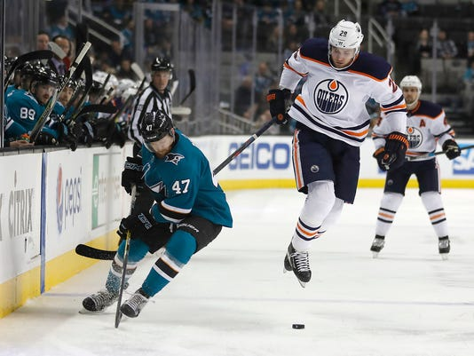 Edmonton Oilers center Leon Draisaitl (29) jumps out of the way from the check by San Jose Sharks defenseman Joakim Ryan (47) during the first period of an NHL hockey game Saturday, Feb. 10, 2018, in San Jose, Calif. (AP Photo/Tony Avelar)