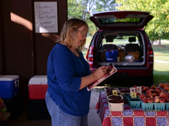 Sue McMaster, of Mac Farms, sets up her stand on Wednesday, Aug. 3, 2016 at the Meridian Township Farmers Market in Okemos.