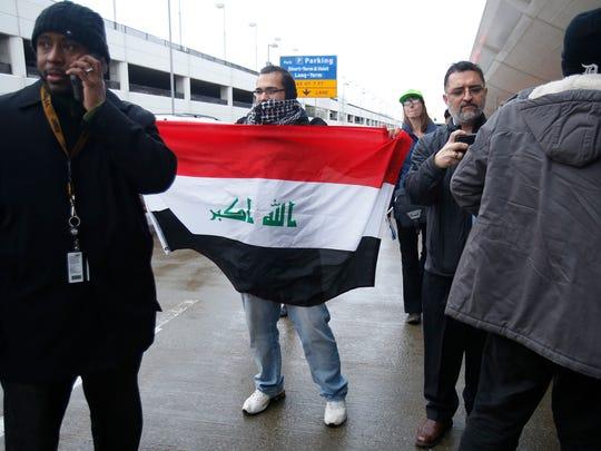 Ameer Aljabiri, 28, of Dearborn, hols an Iraqi flag