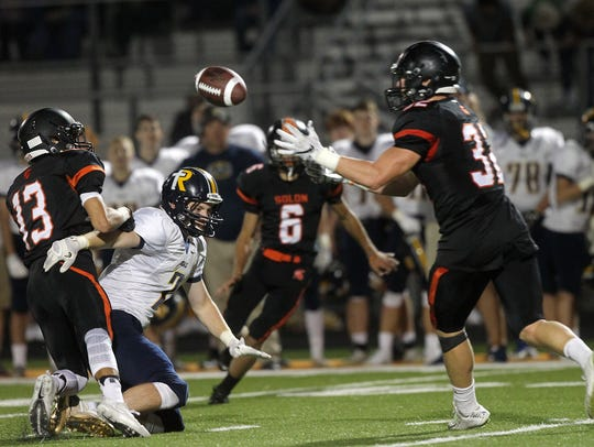 Solon's Adam Bock, right, intercepts a pass that he