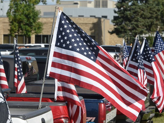Dozens of American flags fly from a row of student vehicles Wednesday, Sept. 6, in the parking lot of Rocori High School in Cold Spring.
