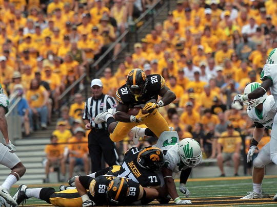 Iowa running back James Butler leaps over a pile of players during the Hawkeyes' game against North Texas at Kinnick Stadium on Saturday, Sept. 16, 2017.