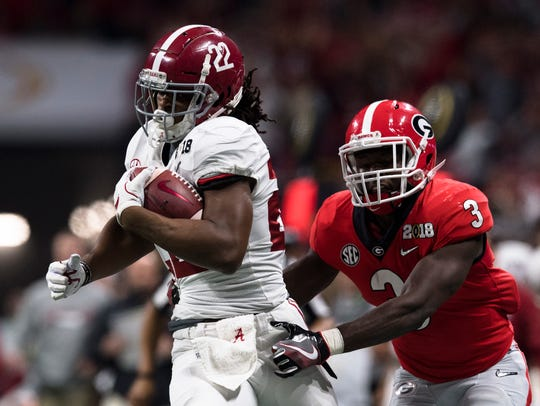 Alabama running back Najee Harris (22) is forced out