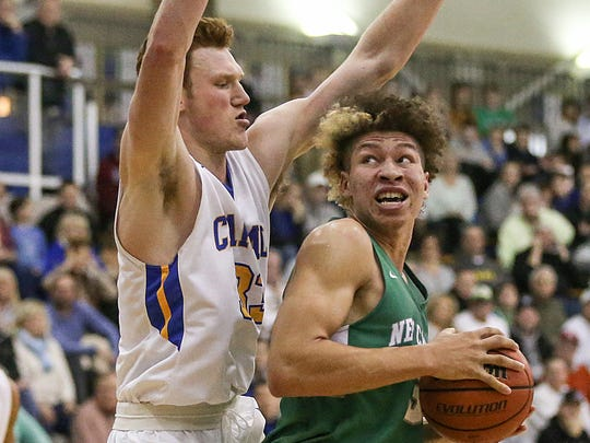 Carmel Greyhounds John Michael Mulloy (33) guards New Castle Trojans forward Mason Gillis (32) as he moves toward the basket during first half action between the Carmel Greyhounds and the New Castle Trojans at Carmel High School, Carmel, Ind., Saturday, Jan. 27, 2018.