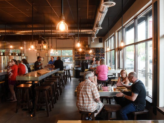 Customers enjoy an evening at Bad Habit Brewing Company Thursday, May 24, at the St. Joseph taproom. The company is close to moving to a new site but the federal government shutdown could delay a needed update to its license.