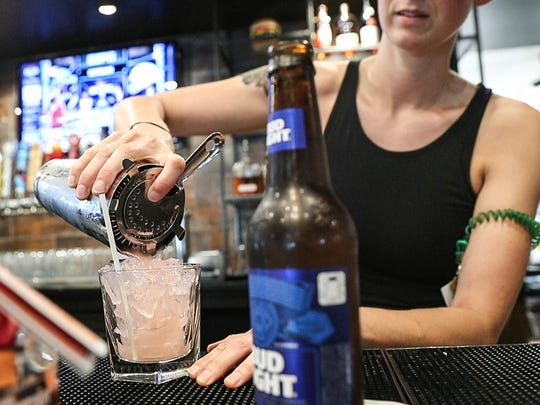 Bru Burger general manager Kayla Morrison pours a drink into a cup with a paper cocktail straw, which is more environmentally friendly than traditional plastic straws, seen at the restaurant on Massachusetts Avenue in Indianapolis, Thursday, June 21, 2018. The restaurant only gives straws to customers who ask for one. Bru Burger is the first Cunningham Group location to use paper straws but they hope to make the change at all of their restaurants soon.