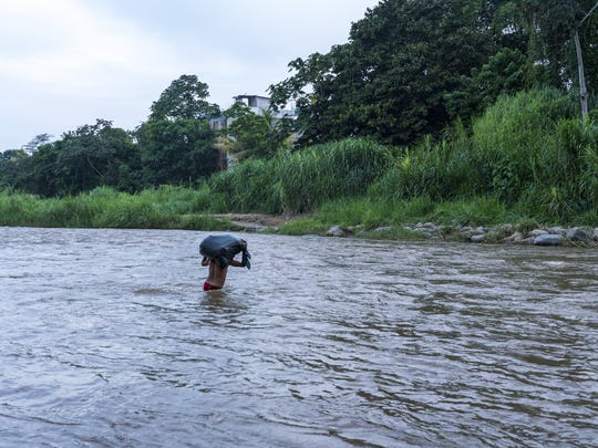 Guatemalans without border crossing cards traverse the Suchiate River by raft or on foot to enter Mexico.