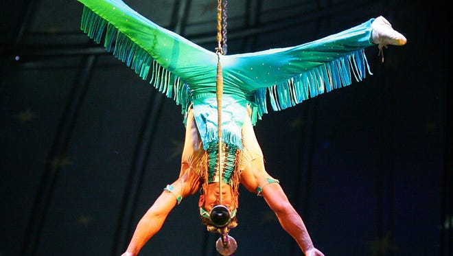 LEFT: A trapeze artist balances himself high above the crowd by just his head during a 2014 performance by the Carson and Barnes Circus at More Life Church on East Main Street in Newark.