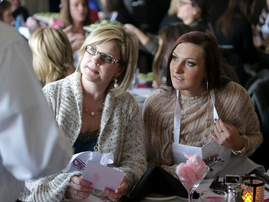 Stacy Giannini (left), and her daughter Brandy Giannini chat with a waiter during a women-only event at Harry and Izzy's