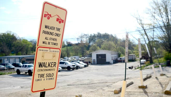 A series of parking spots next to El Torito on Emma Road are marked with signs indicating that the spots belong to Walker Tire, across the street.