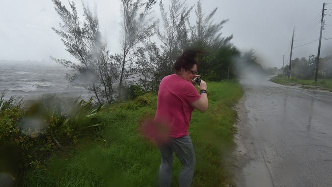Marlene Rosano, of Port St. Lucie, tried to get photos of the stormy weather along Indian River Drive and Walton Road in Port St. Lucie  Sept. 10, 2017, as Hurricane Irma arrived with high winds and flooding rain.