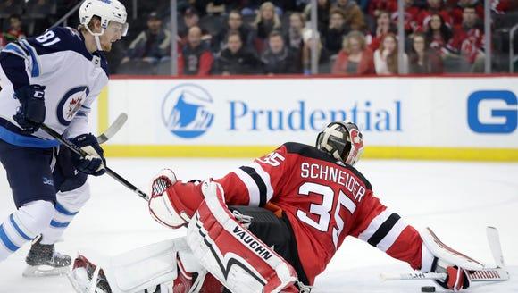 New Jersey Devils goaltender Cory Schneider (35) dives
