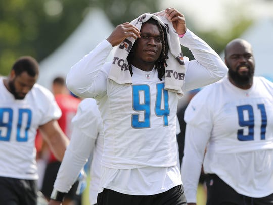 Lions defensive end Ziggy Ansah walks off the field
