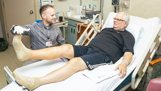 A physical therapist works with a patient after knee surgery.