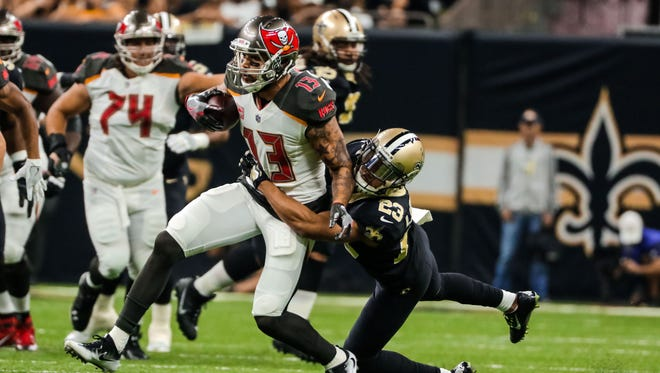 New Orleans Saints cornerback Marshon Lattimore (23) tackles Tampa Bay Buccaneers wide receiver Mike Evans (13) during the first half of a game at the Mercedes-Benz Superdome.