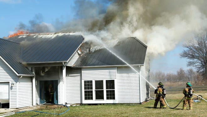Firefighters battle a house fire Saturday near Mulberry, Ind.