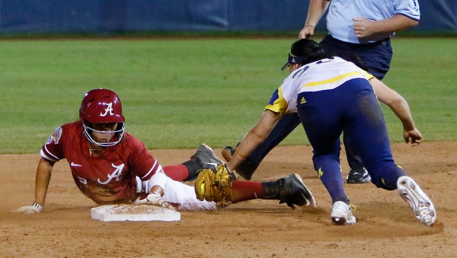 Alabama's Demi Turner, left, safely slides in at second as Michigan's Sierra Romero misses the tag during the sixth inning of a Women's College World Series game in Oklahoma City on Thursday.