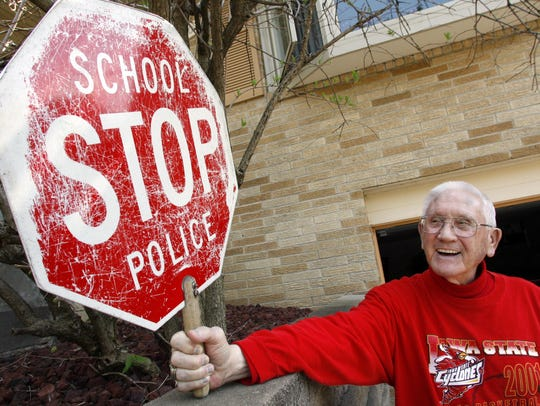 Glen Steward holds his old crossing guard stop sign